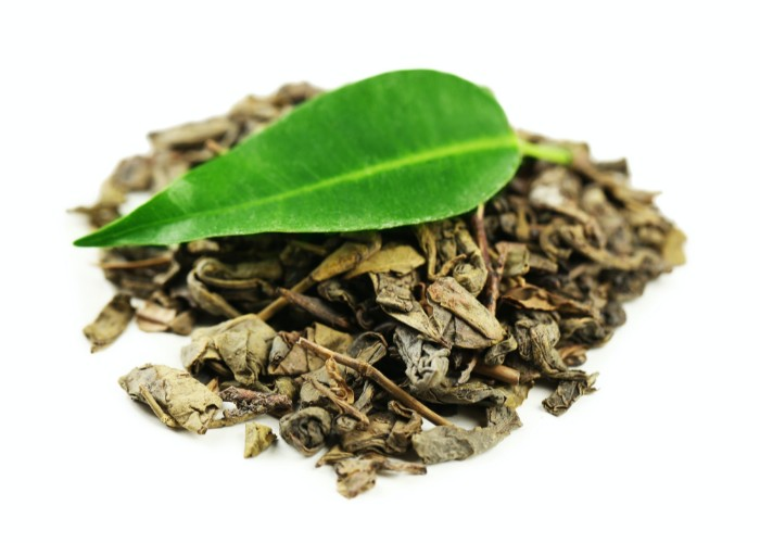 Dried green tea leaves with fresh one on top